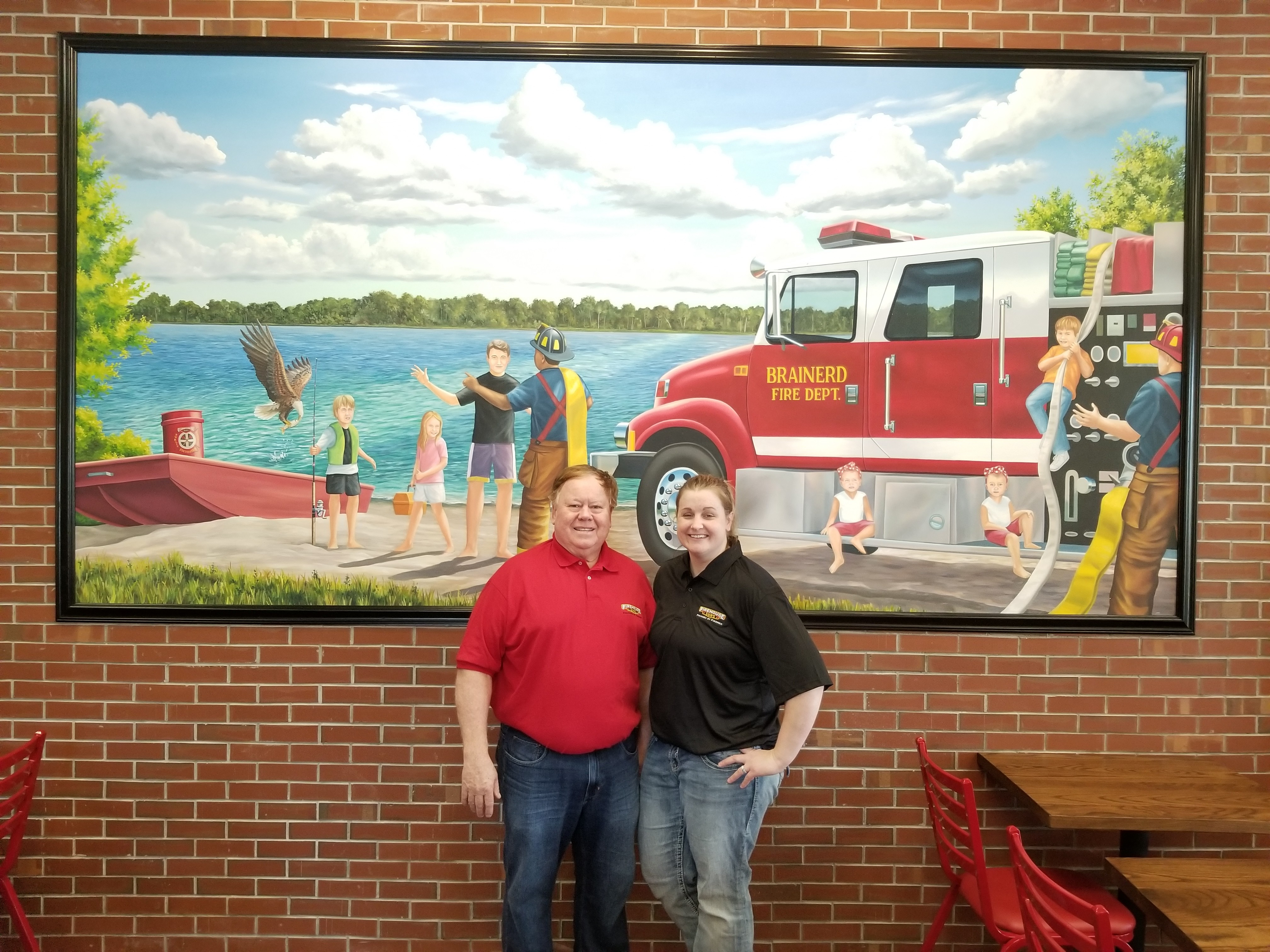 Firehouse Subs operators in front of custom mural